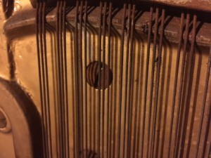 Heavily rusted strings on an old upright